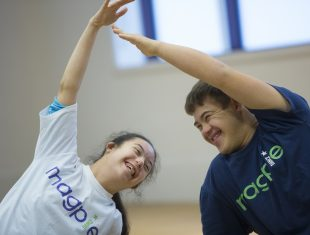 Two people dressed in Magpie Dance T-shirts stand next to each other. They each have their outside arm outstretched up and over their head. They are both smiling.