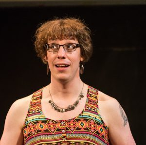 Non-binary white person with brown hair, colourful vest top holding a cup and saucer