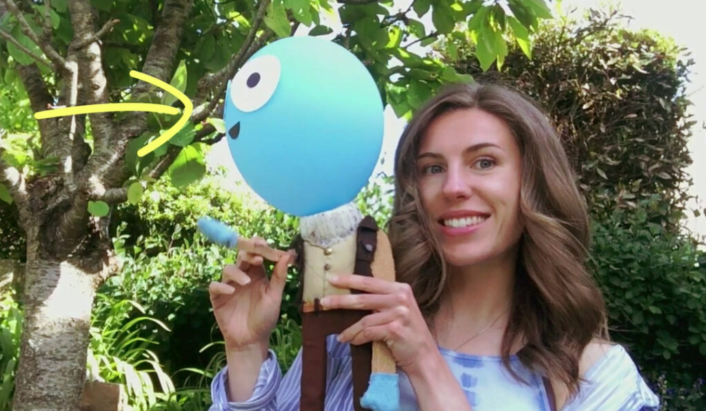 A screenshot of a white brunette woman holding a puppet