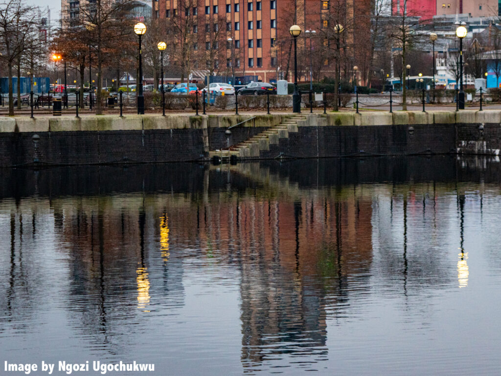 Photo of the side of a canal seen from the other side of the water