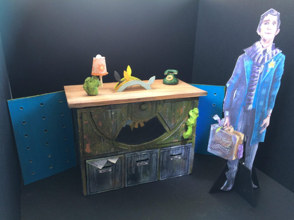 A picture of a small, 3D model of a set. A hotel-desk with astro-turfed squirrels climbing it, beside the desk is a printed costume design to suggest scale.