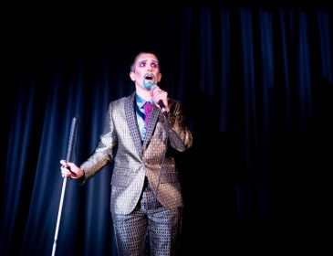 A person wearing a silver and gold suit, with a blue shirt and pink tie. They have a glitter goatee and eyebrows. They are holding a microphone in one hand and the microphone stand in another.