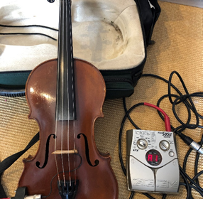 A photo of an electric violin leaning on its case next to cables.