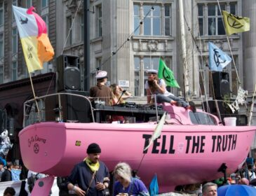 A crowd of people on and around a pink boat in Piccadilly Square in London as part of the Extinction Rebellion demonstrations. Text on the pink boat reads 'Tell the Truth'.