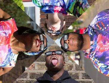 Four band members each wearing a pair of dark glasses with the words 'Buzzin' on them looking up to the sky