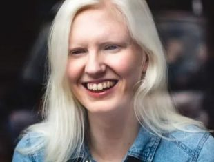 A photo of Ellen, a white woman with blond shoulder length hair. She is wearing a blue denim shirt.