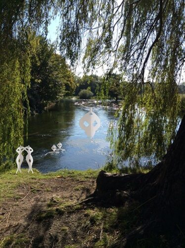 A sunny scene by a river with a tree. Paper ballerinas are superimposed onto the water