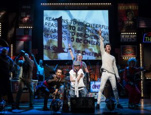 A production photo from Graeae's Reasons to be Cheerful, which shows 3 actors centre stage looking triumphantly straight into the audience. A screen behind them shows text Reasons to be Cheerful repeatedly