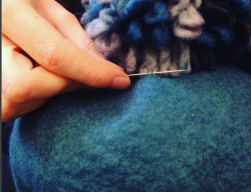 Close up image of a hand sewing felt.