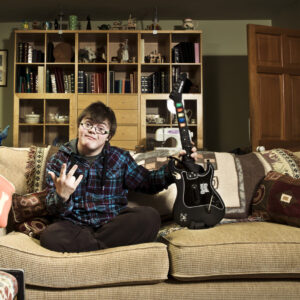 A white man with Down's Syndrome sits on a sofa holding a guitar
