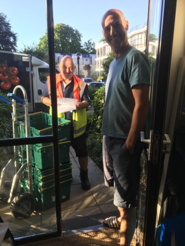 A white bald man stands at a doorway as another white bald man in a tesco delivery uniform stands on the other side with crates of shopping