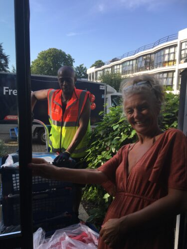 A white woman standing at a door while a black Tesco delivery man brings crates of shopping to it