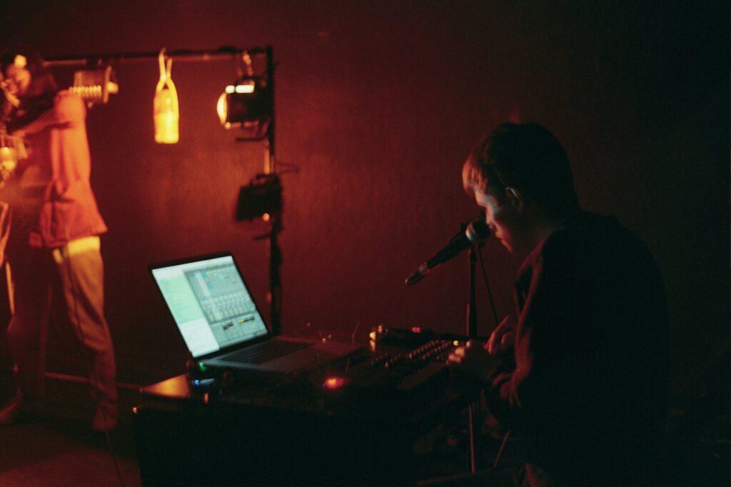 White man sitting at a computer music set up