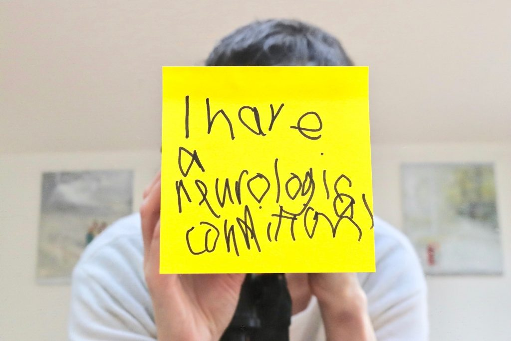 Photograph of a woman overlaid with a sticky note which says I have a neurological condition