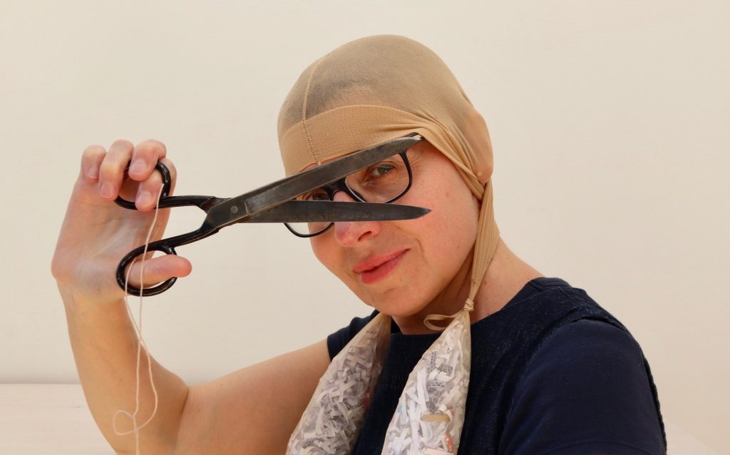 White woman with glasses wearing tights on her head and looking through a pair of open scissors
