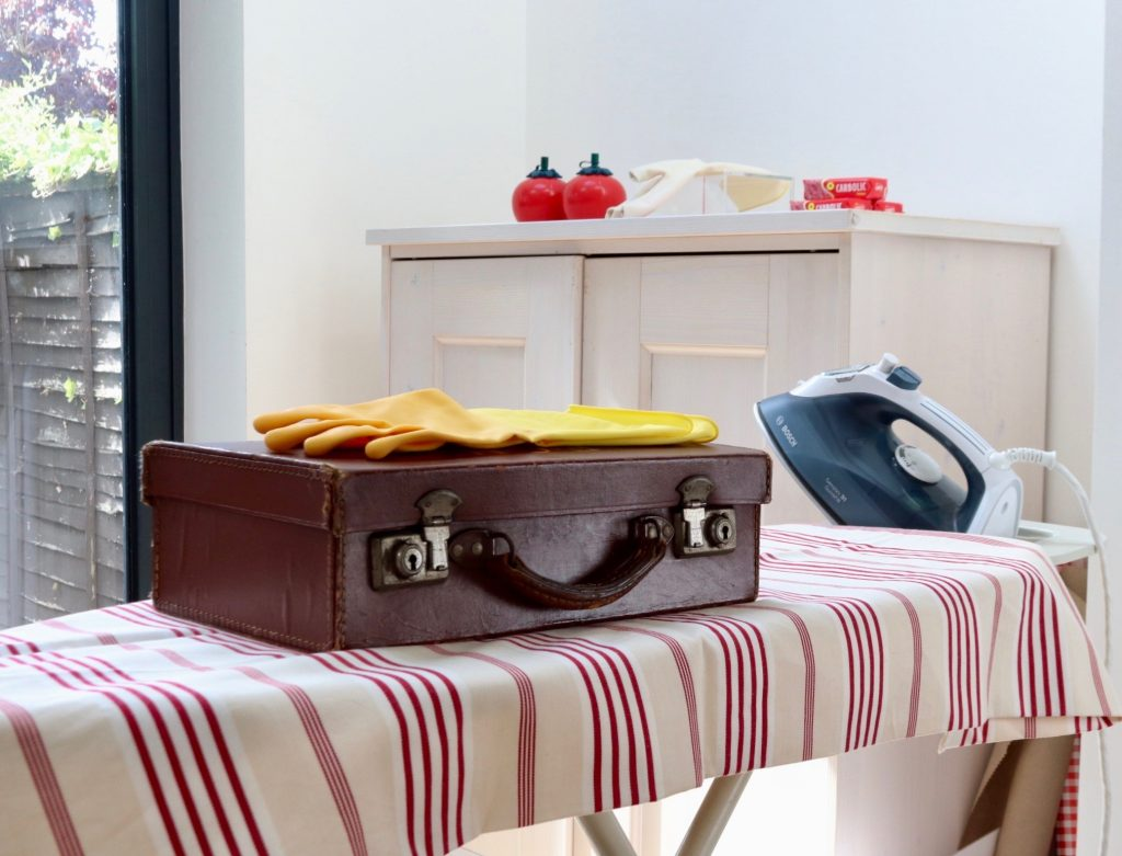 Ironing board with a briefcase which has rubber gloves on it