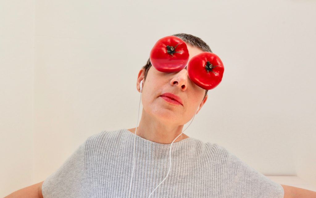 Photograph of a white woman with short grey hair and tomatoes collaged over her eyes