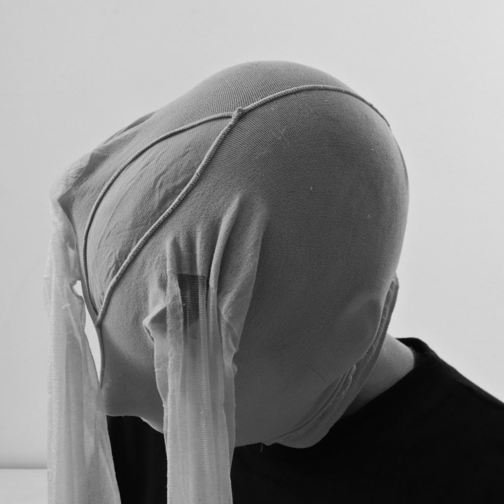 Black and white photo of a woman with tights over her head, looking downwards
