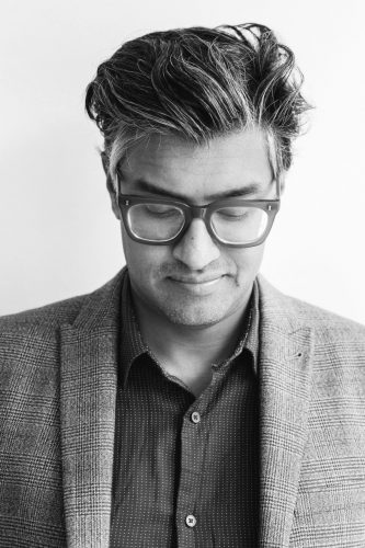 A black and white headshot of Jana. He is wearing a blazer and shirt, his head is pointed down, he is wearing thick rimmed glasses and has swept back hair.