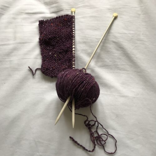 a short block of purple knitting still on the needles. The knitting needles are crossed and sticking out of a ball of purple wool.