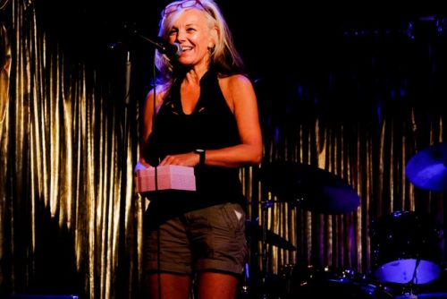 A photo of Liz on stage. She stands at a microphone stand holding a pink box. She is wearing a black vest top and khaki shorts, she has blond shoulder length hair, swept of her face using a pair of red glasses.