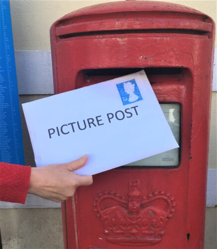 Woman posting a large letter entitled Picture Post into a red post box