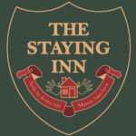 The Staying Inn logo, a shield with gold letters, The Staying Inn. Underneath a latin motto, Salvete ad circulum manentum, se lavate manus! and two palms spread out from a house.