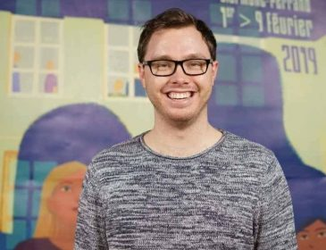 A photo of Tom, a white male with brown hair and black glasses. He is wearing a grey mottled jumper.
