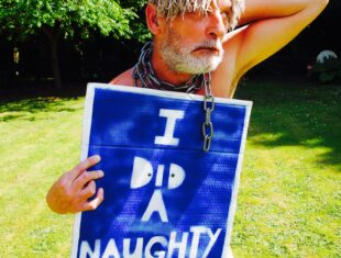 White man with a mop on his head for a wig, he is naked save for a sign which reads, I did a naughty thing.