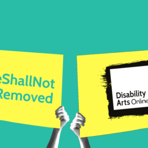 Hands holding up two signs, one has the Disability Arts Online logo, the ther hash the Hashtag We Shall Not Be Removed