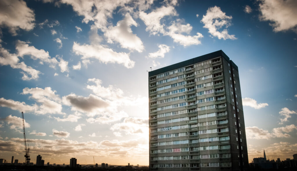 A seventies tower block set against a blue sky