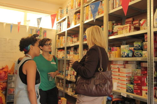 A mixed race woman and two white women stand among packed shelves of food at a foodbank