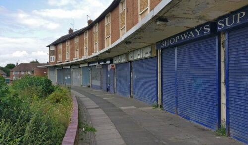 A row of derelict shops with blue shutters down, alongside an overgrown grassy area