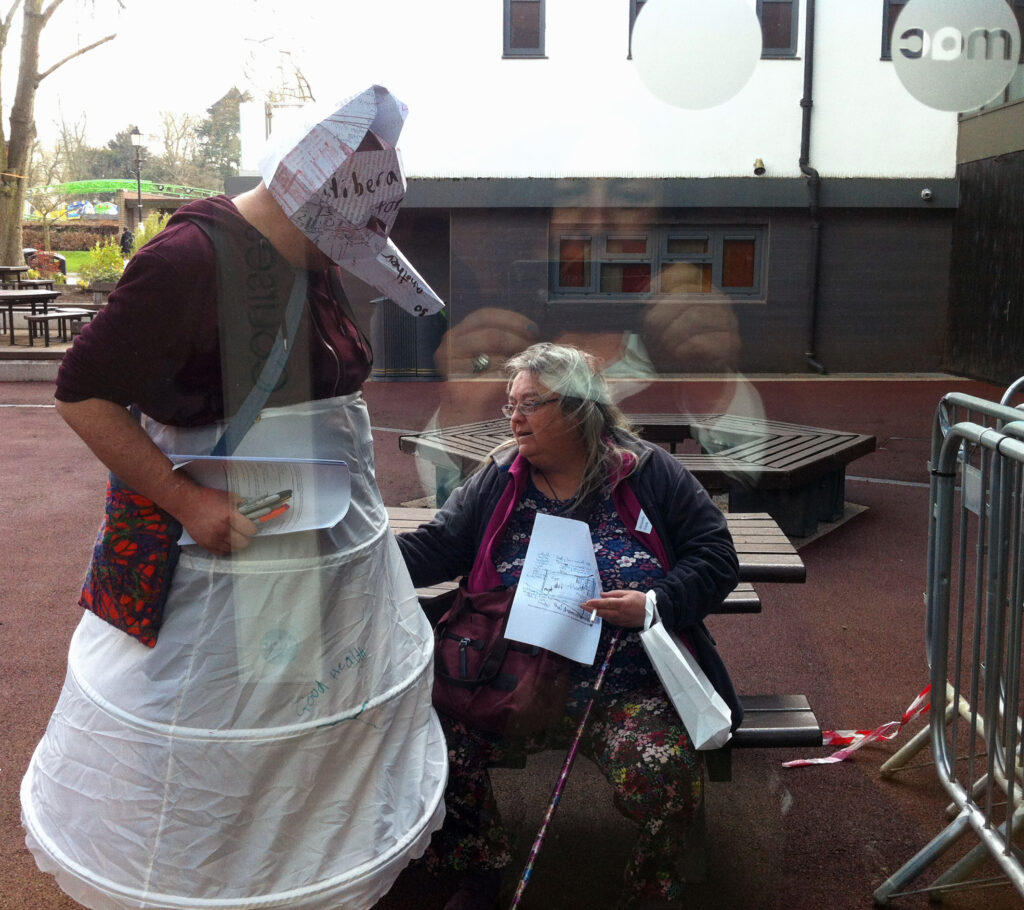 Person wearing a paper hyena mask, and dress made of paper, whilst a woman with a walking stick sits next to them on a park bench