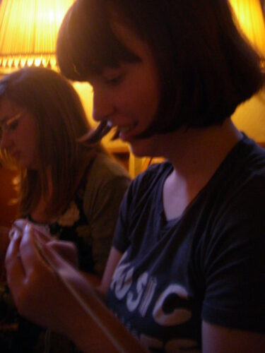 In the foreground a white woman with brown hair is knitting in a dingy pub. She is wearing a grey t shirt with the word music on. The woman is clearly concentrating on her knitting, she  has only managed one or two messy lines. In the background another white woman in knitting, behind the second woman's head is a large glowing lampshade.