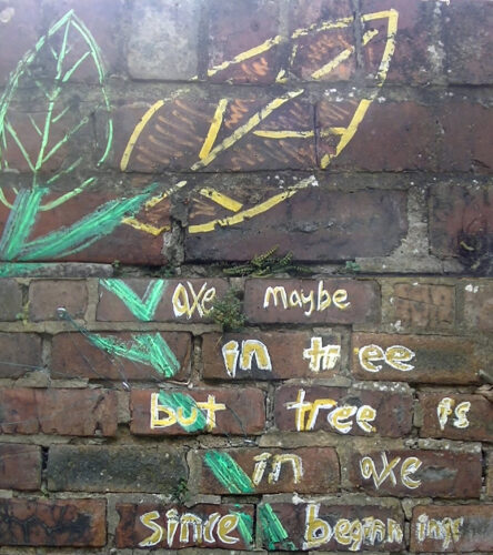 brick wall with chalk drawing of a plant.