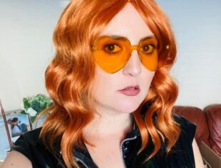 A head and shoulders portrait of Philippa Cole playing the character of Mim. She is wearing an orange wavy wig, orange loveheart sunglasses and a black PVC / wetlook dress.