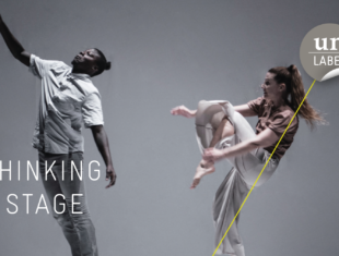"""Two performers, a man and a woman are on one stage. Both stand on square stools. There's text in the left corner. """"Rethinking the Stage."""" The logo of Un-Label is placed in the right corner of the image."""