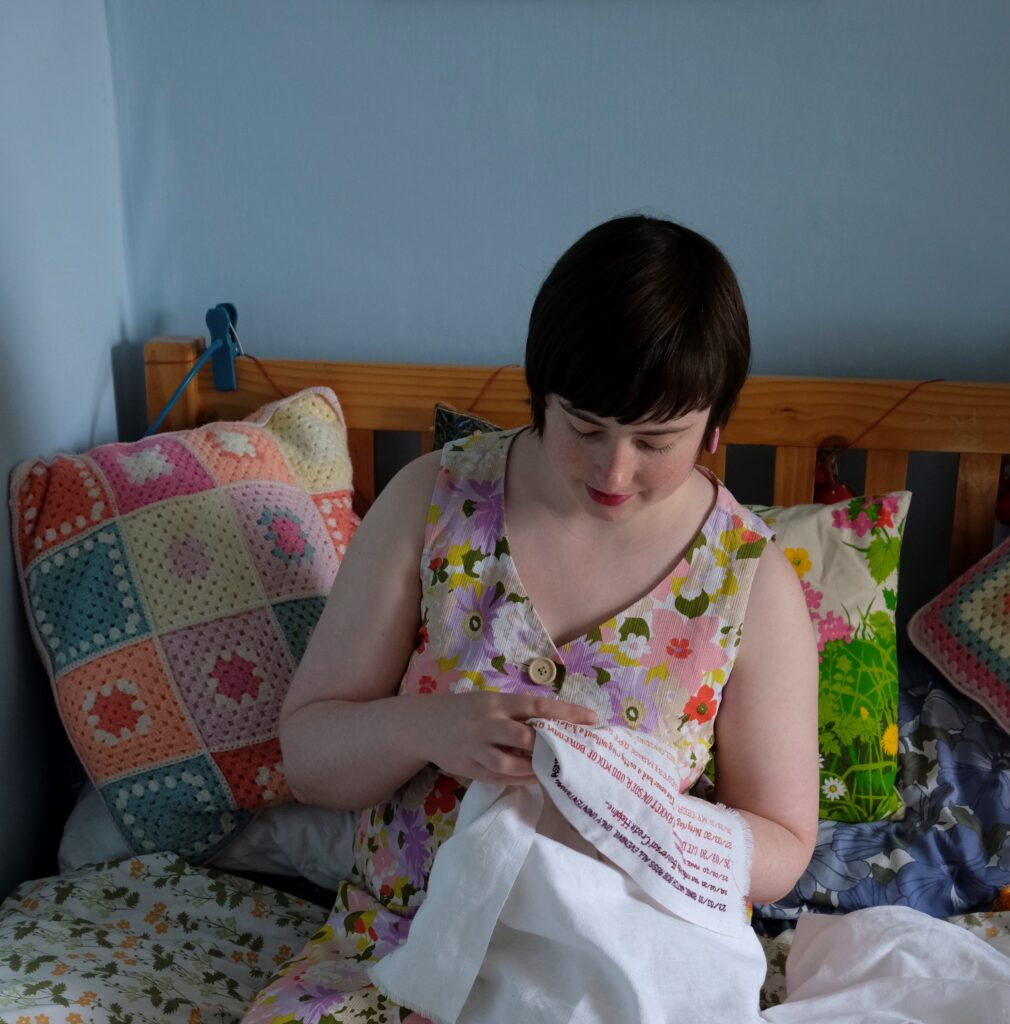 A photograph of the artist, a white woman in her late twenties with dark hair, embroidering her rainbow cross stitch diary entry on to a large white piece of cloth. She is wearing a floral dress and is sitting on her bed, surrounded by colourful cushions.