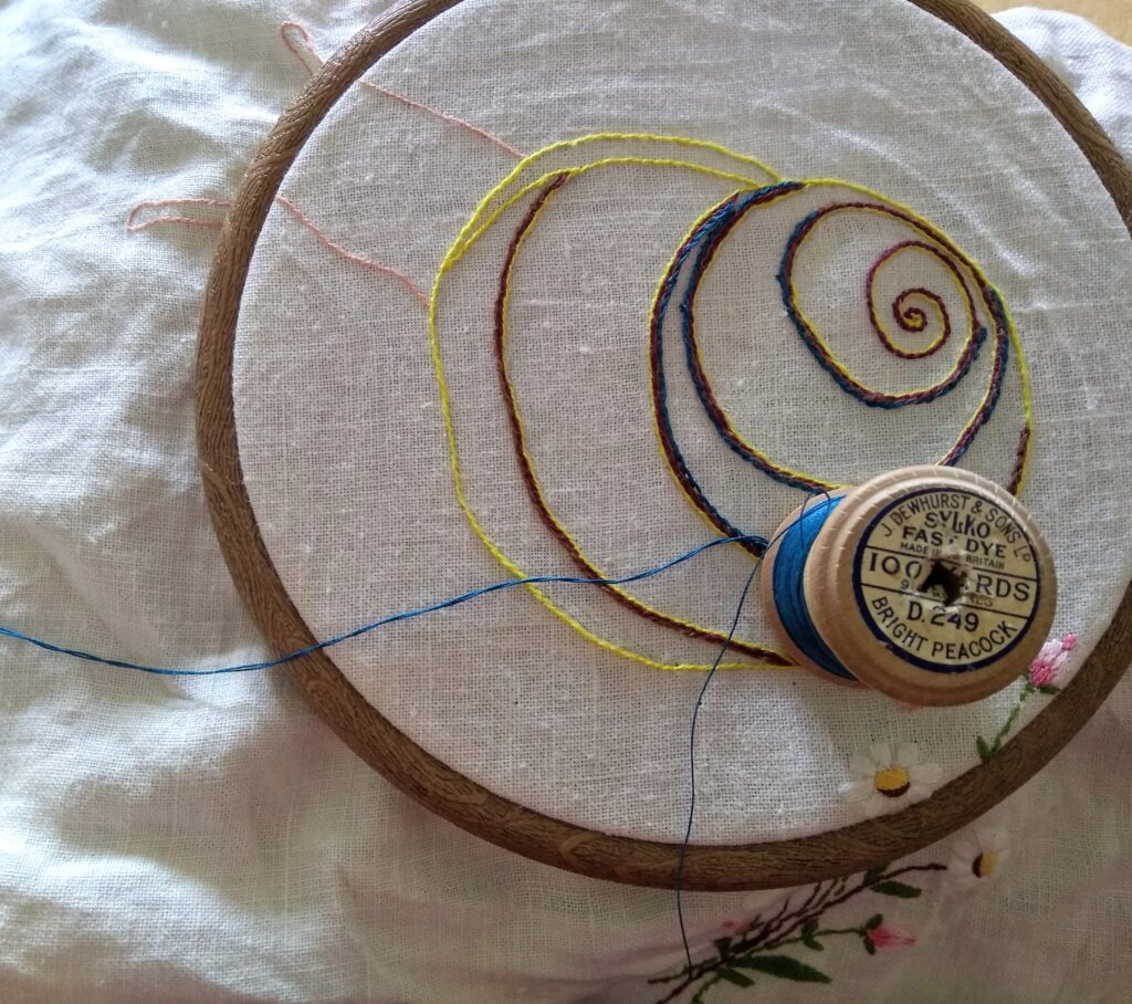 A photograph of the beginnings of a snail embroidery on an old piece of hand embroidered linen, held in an embroidery hoop. There is an old wooden bobbin on top of the embroidery, holding a reel of blue thread
