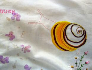 Photograph of an embroidered snail