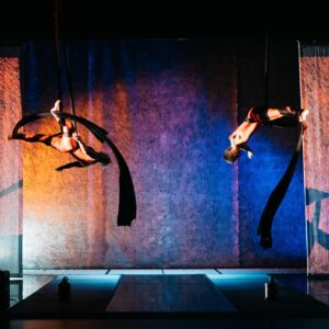 A wide landscape shot of two women on aerial silks mid-fall