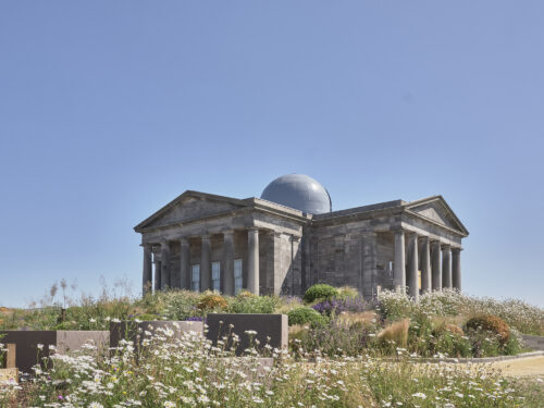 City Observatory, Collective, Calton Hill, photographed in summer with wildflowers and blue sky