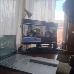 A white man smiles at the cmaera, he has two computer screens set up with various windows of Zoom and Skype calls open