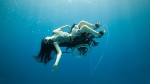 A woman sat in a wheelchair wearing a white dress. She is underwater and is floating sideways with her right arm outstretched towards the camera. Her long hair flows behind her.