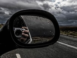 Photograph shot in a car's wing mirror of a person holding a camera