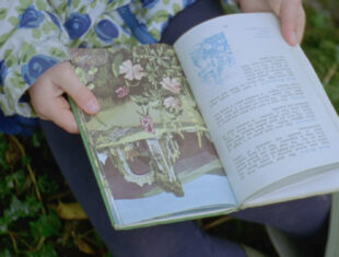 Still from a film of a woman holding British Wild Flowers in their hands