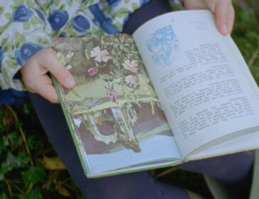 still of a Ladybird book being held open by a pair of hands