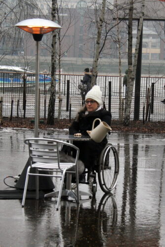 photo of an artist in a wheelchair, with a jug, taken outside on the south bank of the river thames