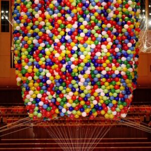 photo of thousands of brightly coloured balloons in a church attached to artist Noemi Lakmaier